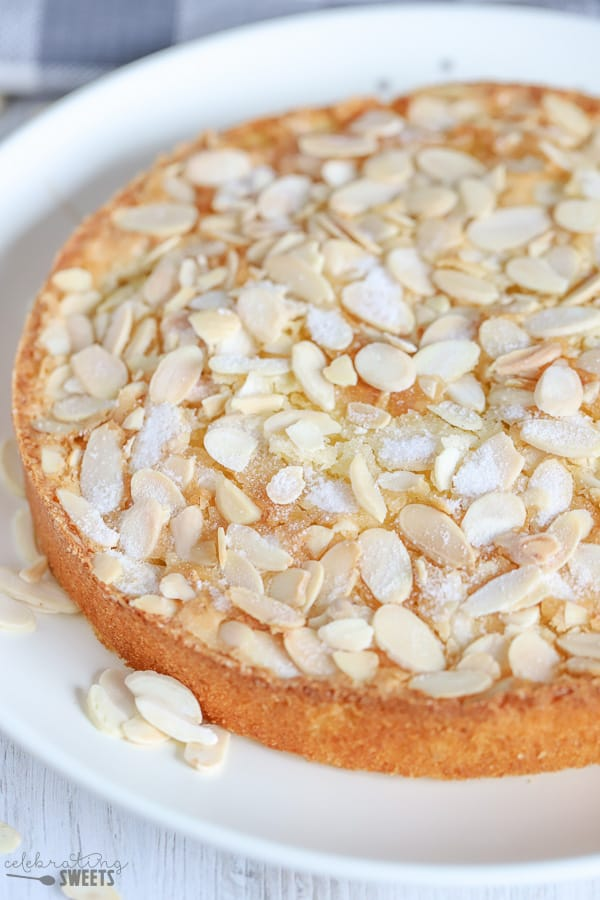 Single layer cake topped with sliced almonds on a white plate.