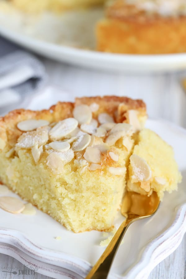 A slice of cake topped with sliced almonds on a white plate with a gold fork.