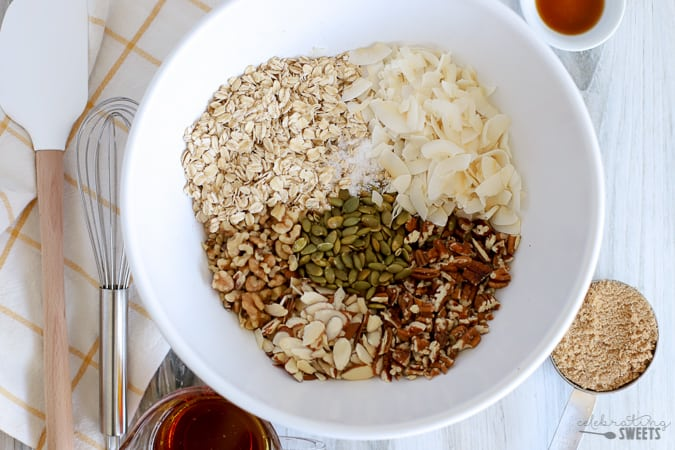 A large white bowl filled with ingredients for granola: oats, nuts, seeds, coconut.
