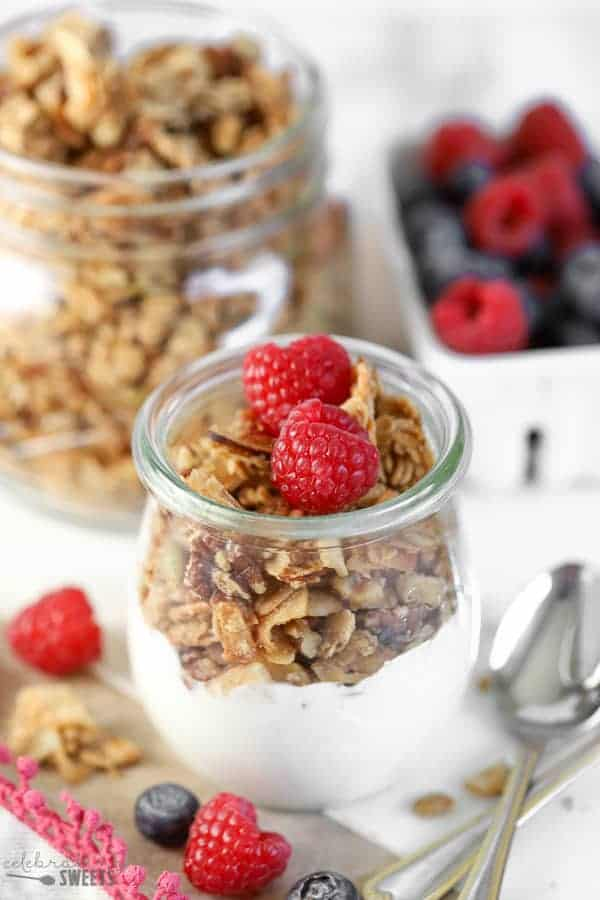 Glass jar filled with yogurt, granola and topped with raspberries.