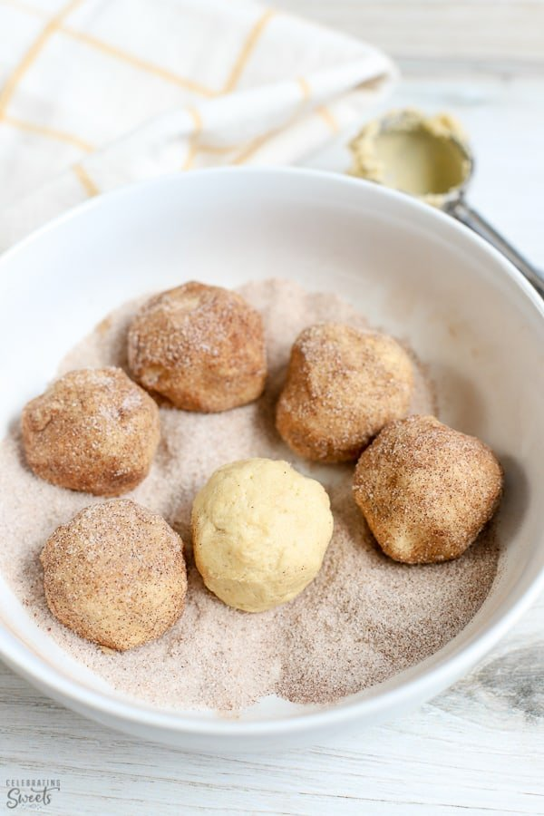 Six cookie dough balls in a large white bowl filled with cinnamon sugar.