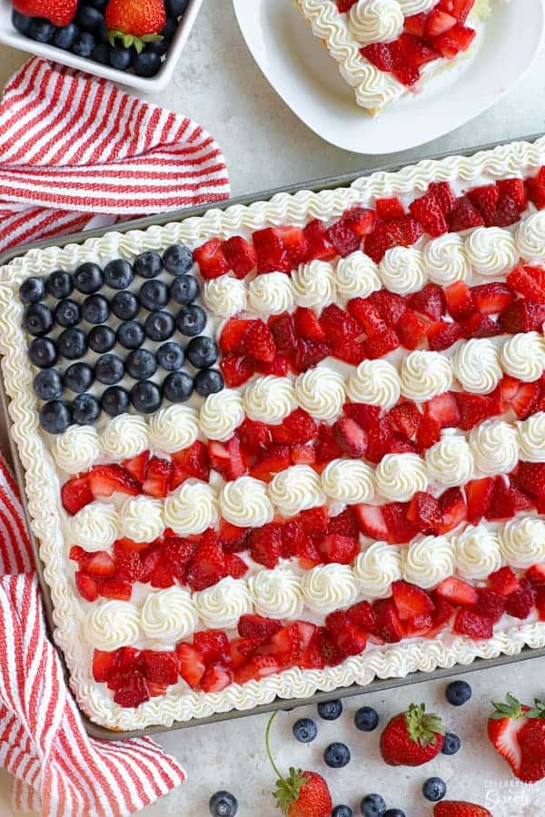 American flag cake decorated with strawberries, blueberries and white frosting.