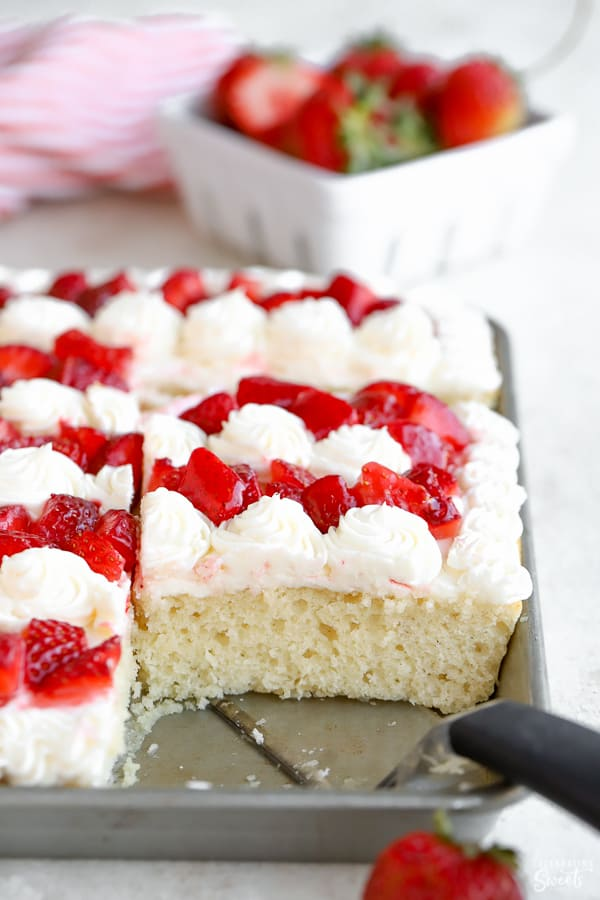 Vanilla sheet cake topped with vanilla frosting and chopped strawberries.