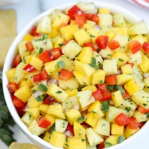 Pineapple mango salsa in a large white bowl.