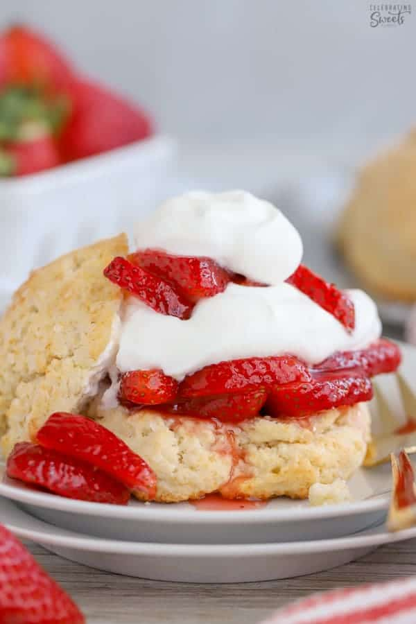Strawberry Shortcake on a white plate with a gold fork.