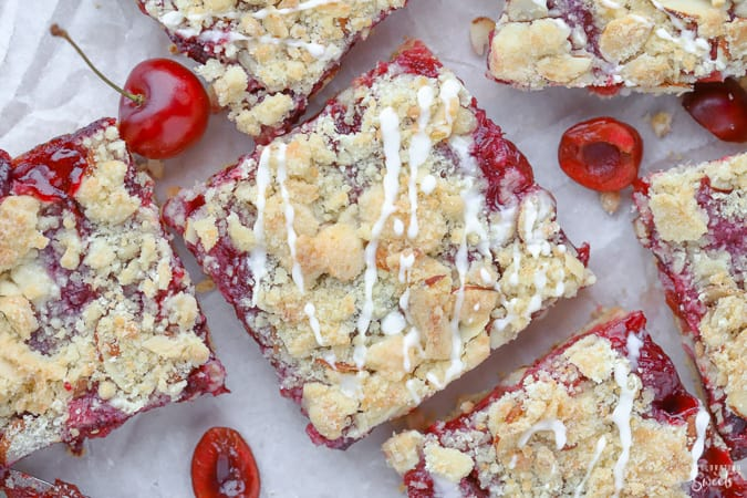 Almond Cherry Streusel Bars on parchment paper,
