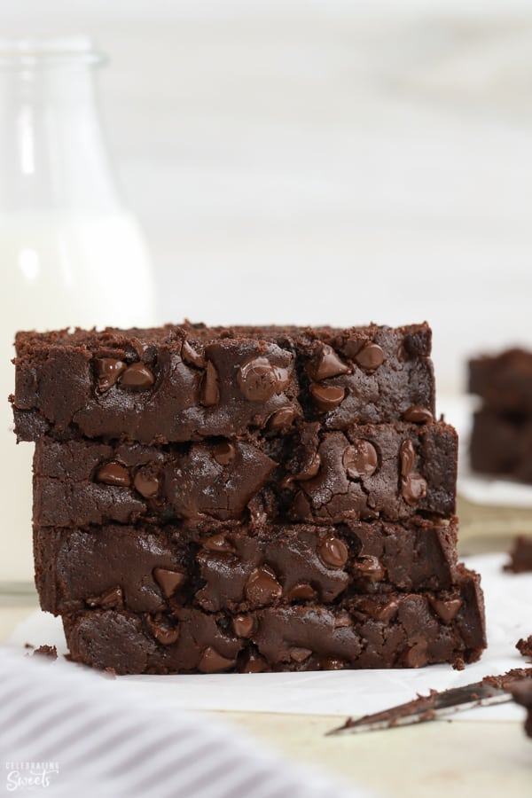 A stack of four slices of chocolate zucchini bread with a glass of milk in the background.