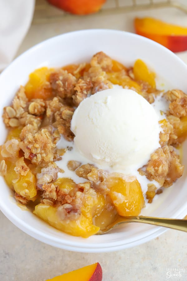 Peach crisp in a white bowl with a scoop of vanilla ice cream.