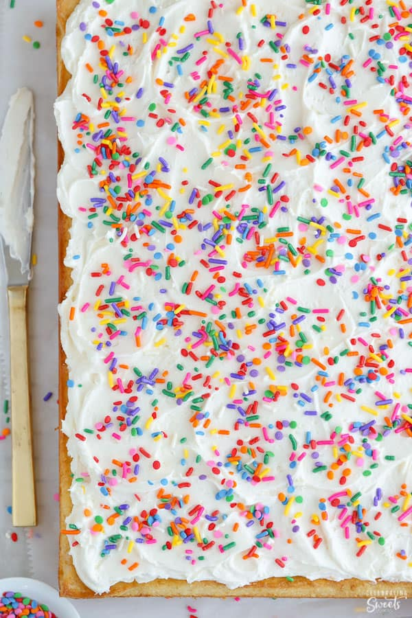 Vanilla sheet cake topped with vanilla frosting and sprinkles.