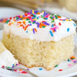 Slice of vanilla cake with vanilla frosting and sprinkles on a white plate.