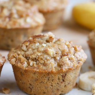 Banana Nut Muffin on a white board surrounded by muffins and sliced banana.