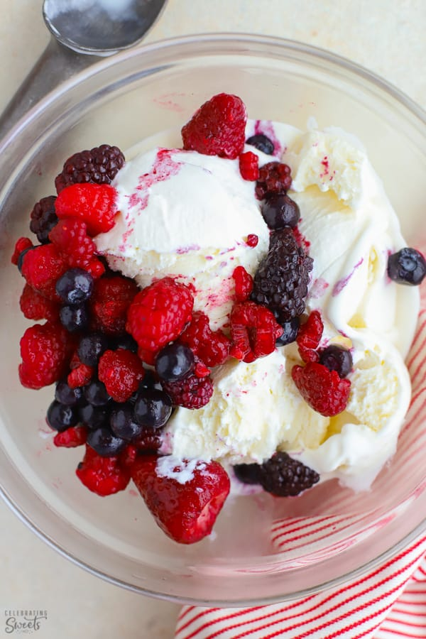 Large bowl of vanilla ice cream topped with frozen berries.