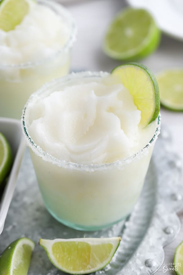 Frozen margarita in a glass on a grey platter.