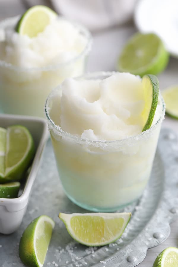 Frozen Margarita garnished with lime on a grey platter.