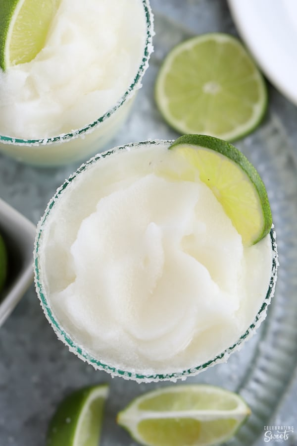 Frozen margarita in a glass garnished with lime.