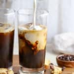 Milk being poured into iced coffee