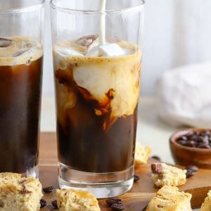 Two glasses of iced coffee with cream being poured in.