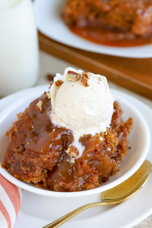 Pumpkin cake on a white plate topped with caramel and vanilla ice cream.