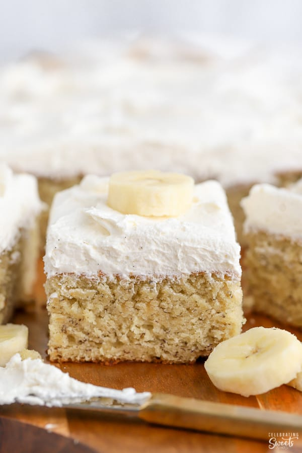 Slice of banana cake topped with vanilla frosting and sliced banana.