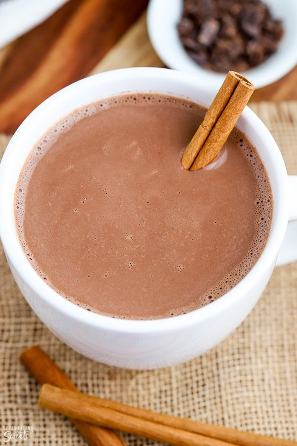 Mexican Hot Chocolate in a white mug garnished with a cinnamon stick.