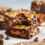 Two caramel brownies on a piece of parchment paper.