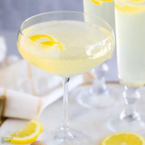 Light yellow French 75 cocktail in a champagne glass topped with a lemon twist.