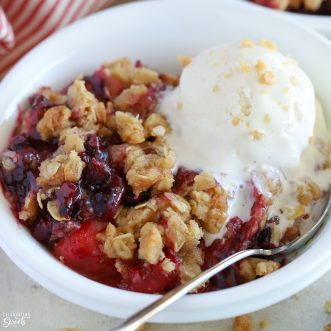 Berry crisp in a white bowl topped with vanilla ice cream.