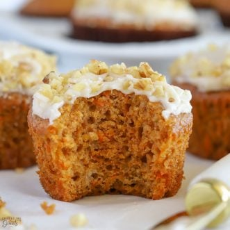 Carrot muffin topped with frosting and walnuts.