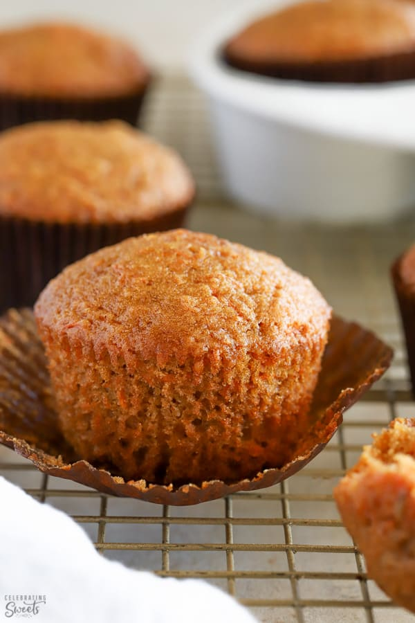 Carrot muffin in a brown cupcake wrapper on a wire rack.