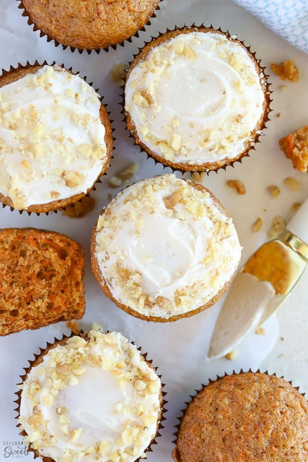 Carrot cake muffins topped with white frosting and chopped walnuts.