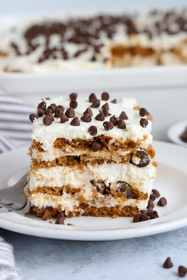 A slice of icebox cake topped with chocolate chips on a white plate.