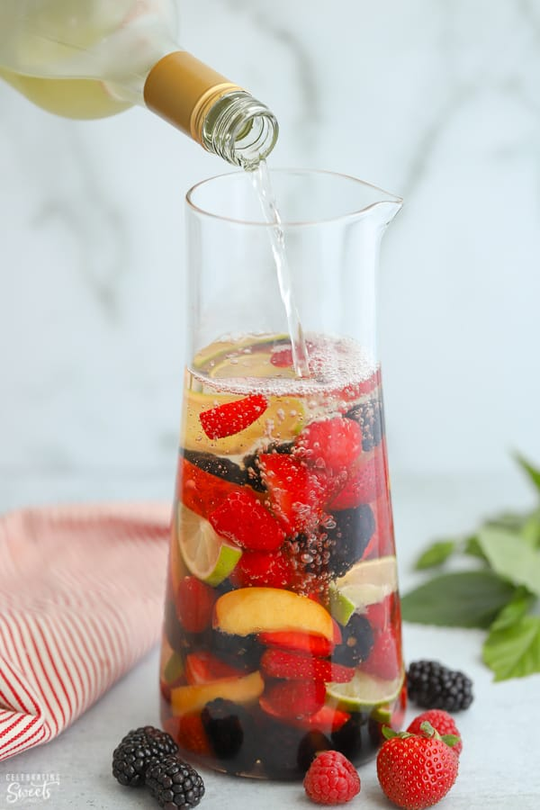 Pitcher of white sangria filled with peaches, berries and sliced lime.