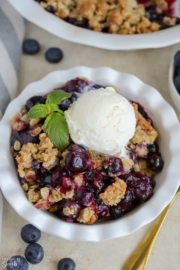 Blueberry Crisp topped with ice cream in a white bowl.