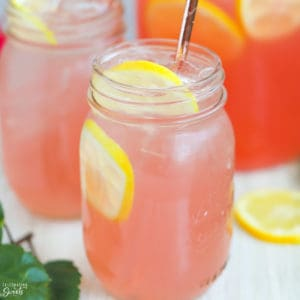Mason jar filled with pink lemonade and lemon slices.