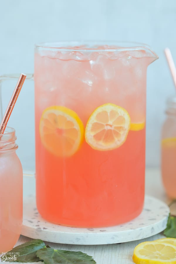 A pitcher filled with pink lemonade, ice, and lemon slices.