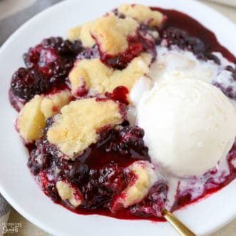 Blackberry Cobbler on a white plate with a scoop of vanilla ice cream.
