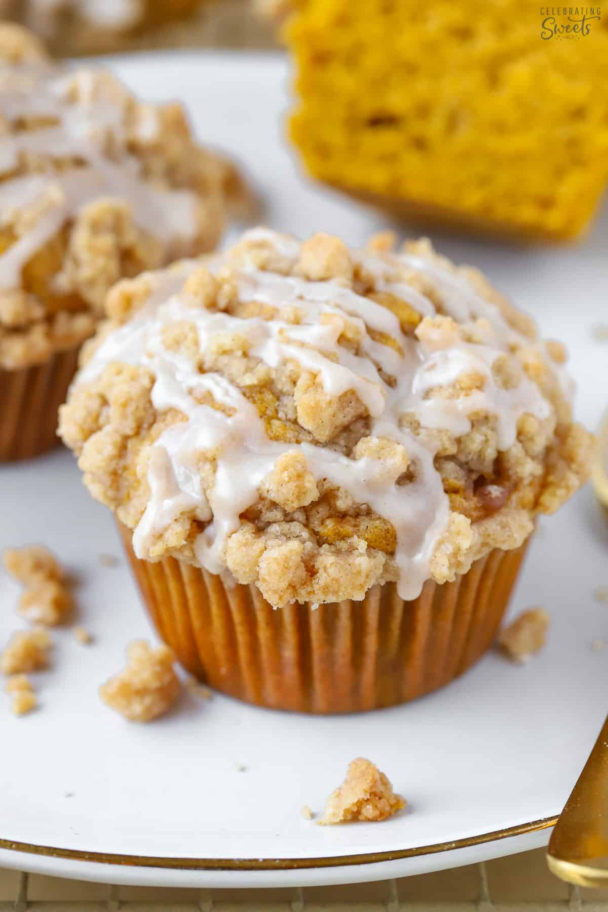 Pumpkin muffin with crumb topping and white icing on a white plate.