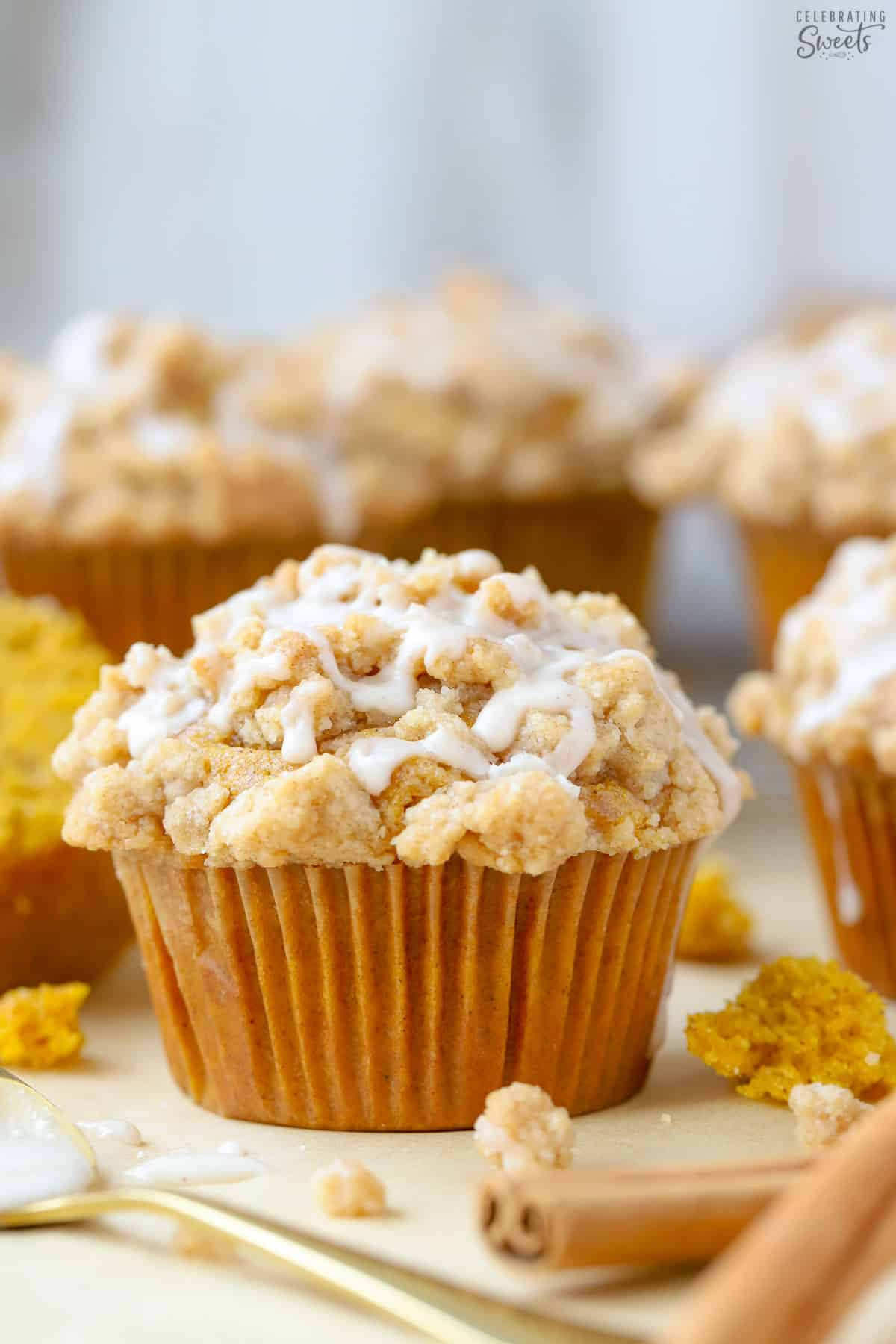 Pumpkin muffin on parchment paper surrounded by cinnamon sticks and a spoon of icing.