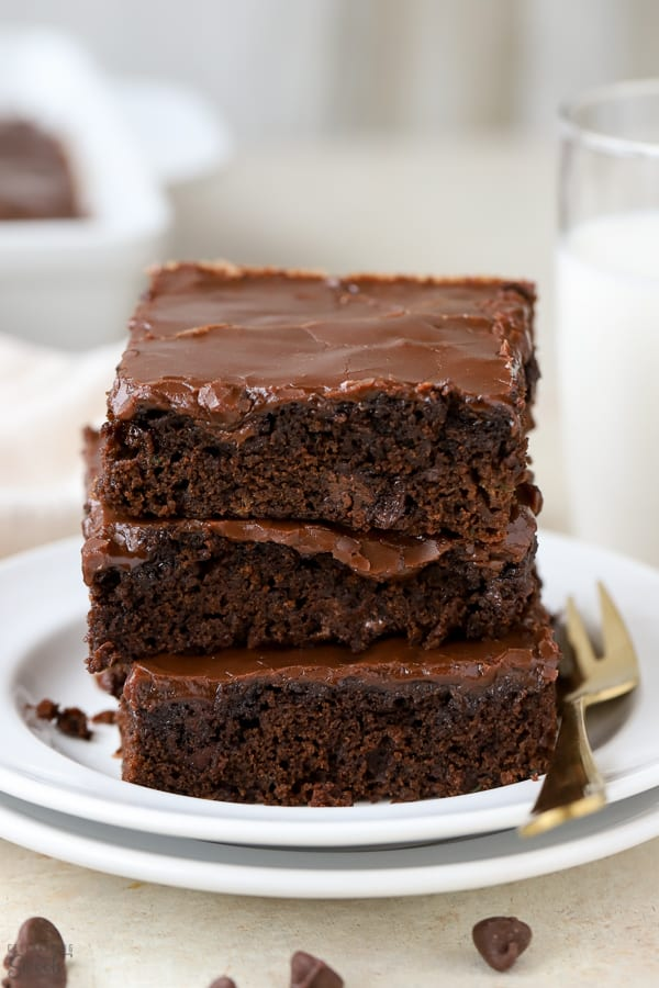 Stack of three brownies on a white plate.