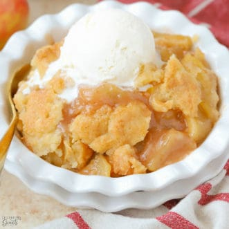 Apple cobbler in a white dish topped with vanilla ice cream.