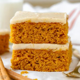 Stack of pumpkin bars on parchment paper.