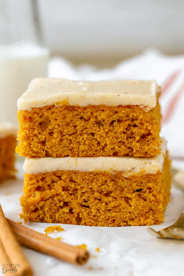 Sliced pumpkin bars topped with frosting on a piece of parchment paper.