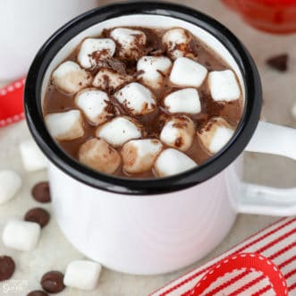 Hot chocolate in a white mug topped with marshmallows.