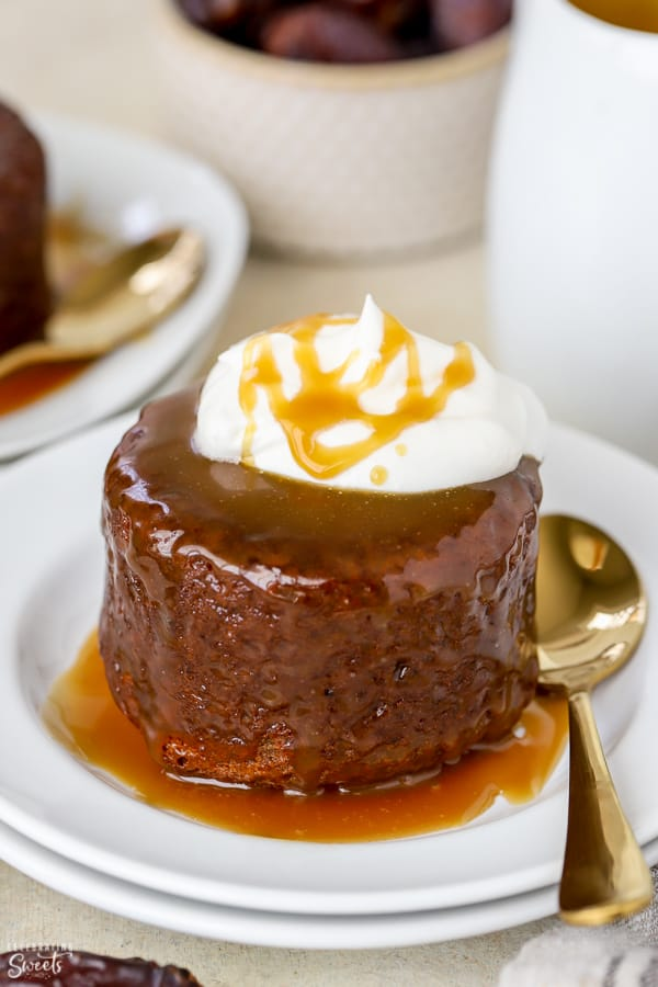 Sticky toffee pudding cake on a plate with a gold spoon.