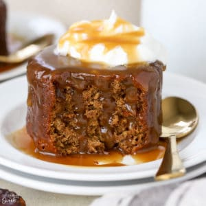 Sticky toffee pudding cake on a white plate topped with whipped cream.