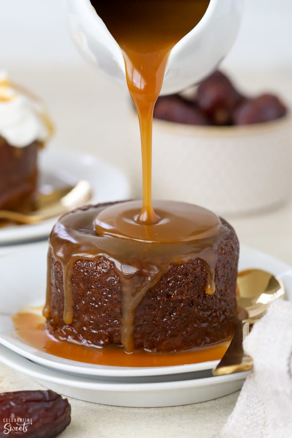 Toffee sauce being poured over an round cake on a white plate.