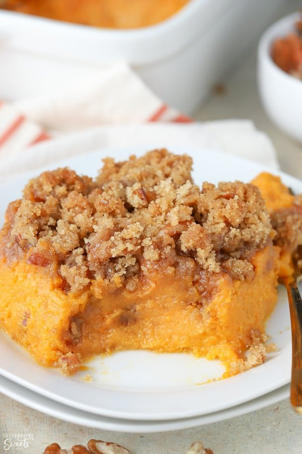 Sweet potato souffle on a white plate with a gold fork
