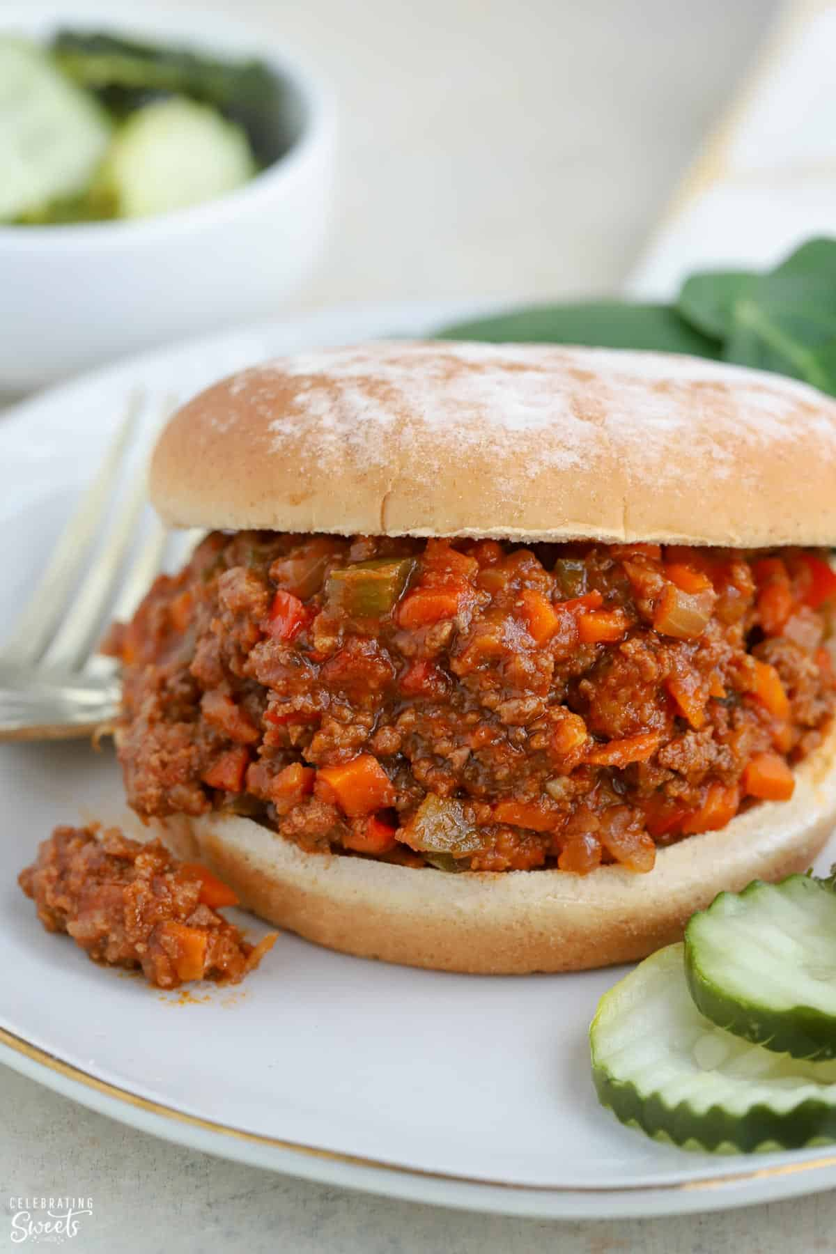 Sloppy joe sandwich on a plate with pickles