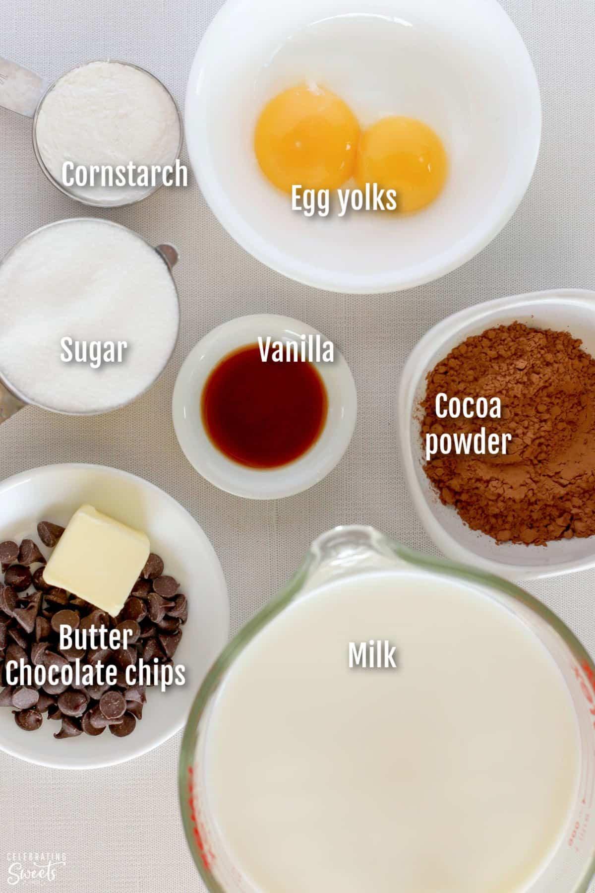 Ingredients for making chocolate pudding (milk, sugar, chocolate, butter, vanilla, cornstarch, egg yolks)