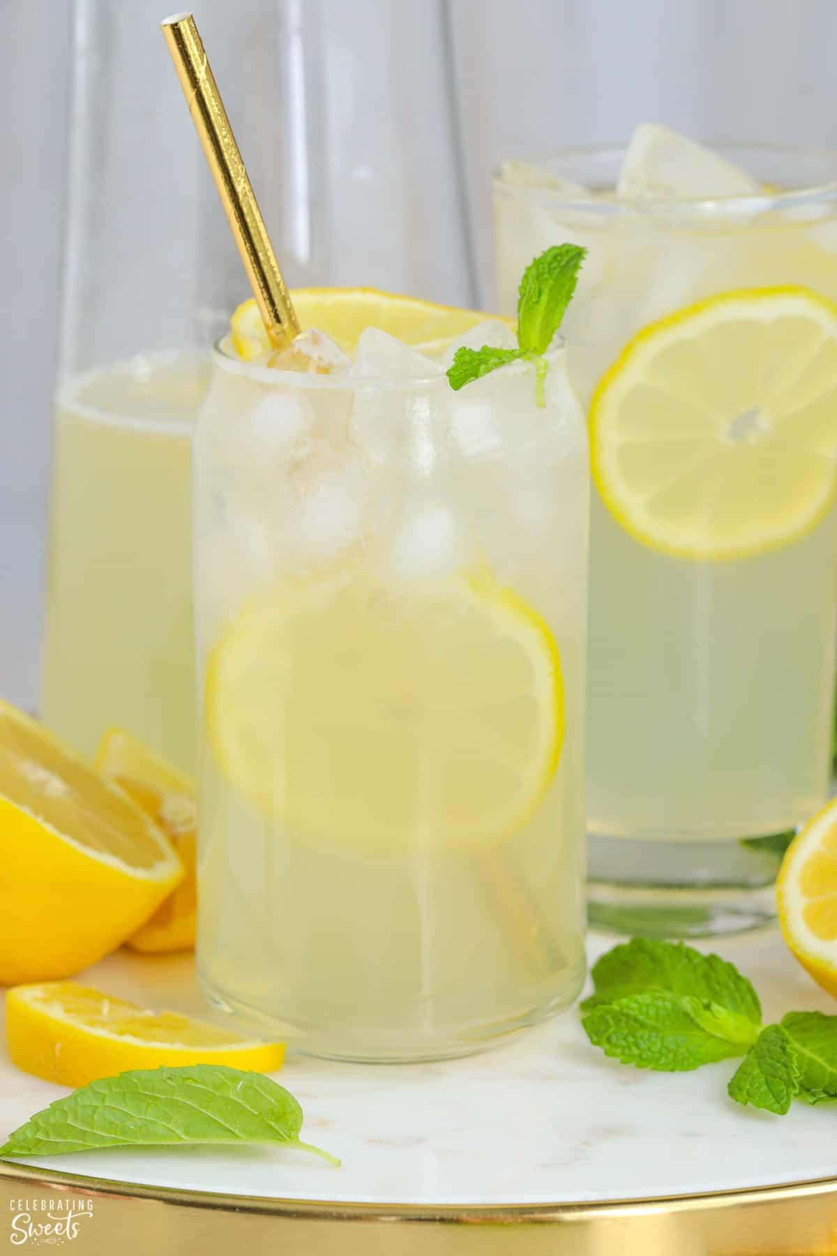 Glasses of lemonade garnished with lemon slices and mint.